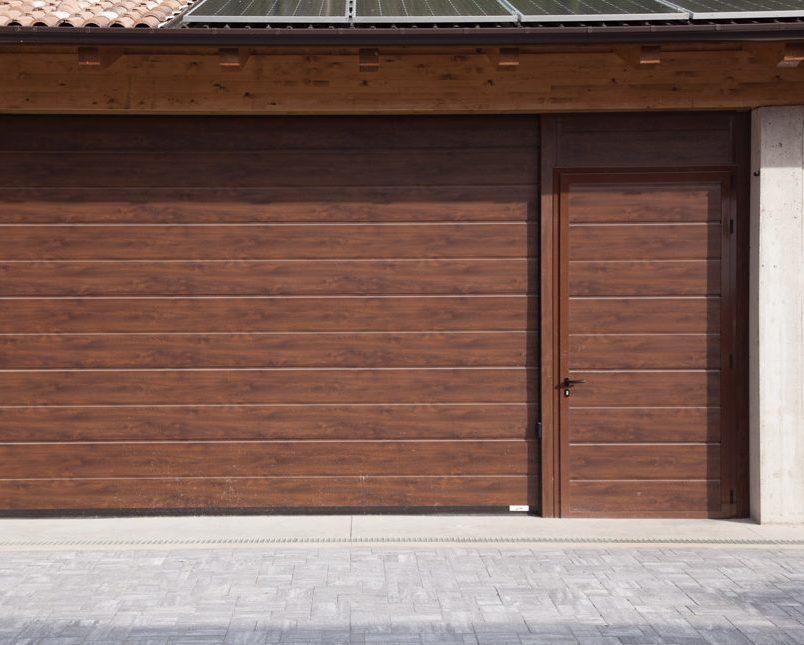 Portone per garage in tinta legno con porta pedonale di accesso Iridium Doors