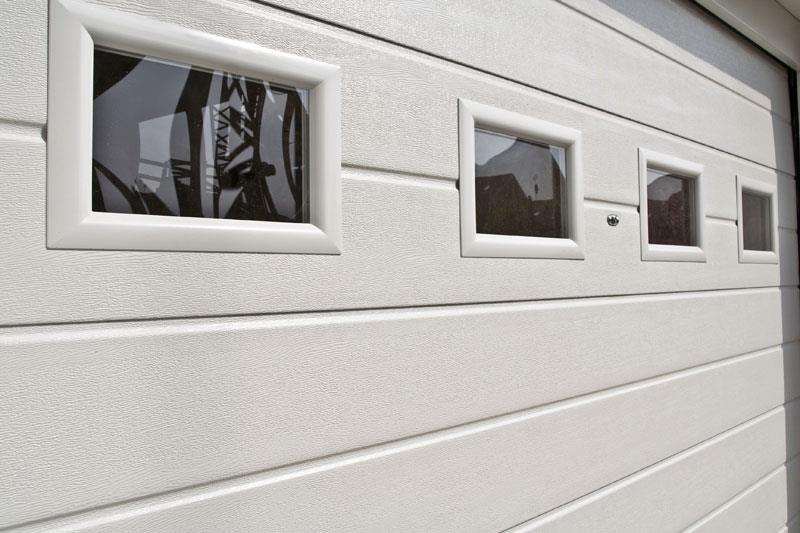 Portone sezionale per garage bianco con dettaglio finestratura modello alcor